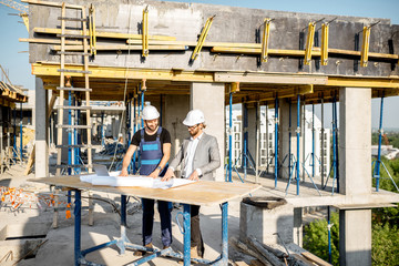 Engineer with worker in uniform working with architectural drawings at the table on the construction site outdoors
