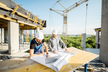 Engineer with worker in uniform working with architectural drawings and laptop at the table on the construction site outdoors