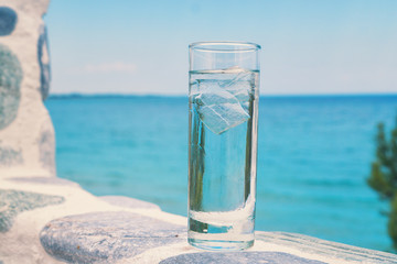 Glass of water with ice on the beach