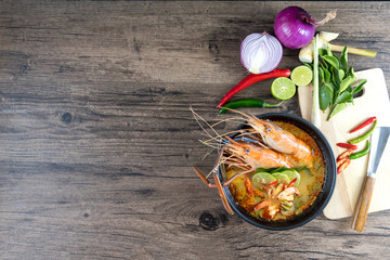 Close up Asian Spicy soup with shrimp in bowl , famous Thai food cuisineม Tom Yum Goong Spicy Sour Soup on wooden table top view