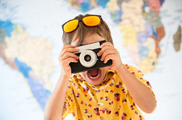 funny delightful little boy with vintage camera on world map background