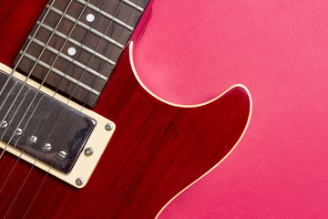 Close-up of red electric guitar on pink background. Musical concept of guitar music.