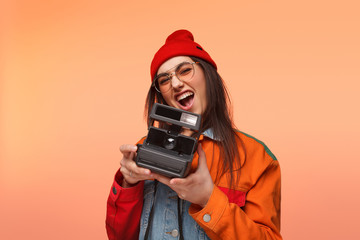 Expressive hipster girl with retro camera
