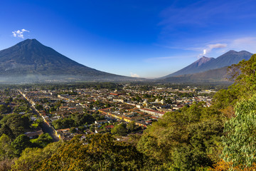 Guatemala. Antigua. Panoramic view of the city and surrounding volcanoes (from left to right): dormant Agua, smoky Fuego and Acatenango