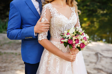 Wedding couple in love. Groom embrace bride with wedding bouquet