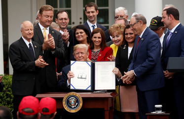 "U.S. President Trump displays the signed ""VA Mission Act of 2018"" during signing ceremony at the White House in Washington"