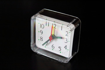 A square clock with an alarm clock in a plastic transparent case on a black surface. Close-up. Isolated. Background.