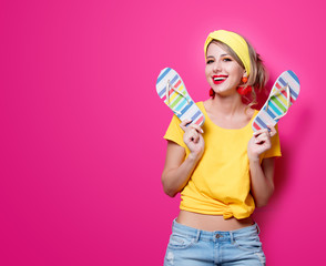Young redhead girl in yellow clothes with vacation flip flops on pink background. Clothes in 80-s style