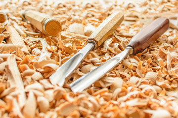 Chisels laid in wooden shavings on the desk. Carving tools lying in the shavings. In a carving workshop. Cutting of linden wood. Wooden gavel on a work pontoon in a carving workshop.