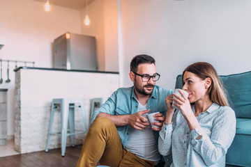 Couple drinking tea of coffee on the floor in their apartment.