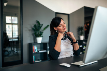 Charming relaxed woman with headphones sitting in front of computer screen.