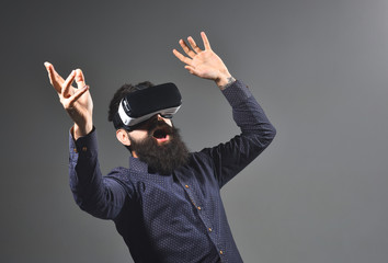 Excited attractive man using 3d goggles watching virtual reality. Surprised bearded man with VR device. Amazed guy touching air during using VR-glasses virtual reality headset. Virtual reality glasses