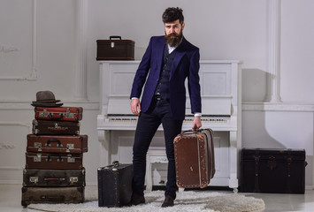 Baggage delivery concept. Macho elegant on strict face stands near pile of vintage suitcase, holds suitcase. Man, traveller with beard and mustache with luggage, luxury white interior background.