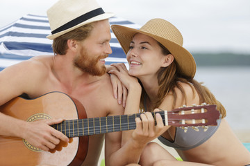 couple having fun and playing guitar on the beach