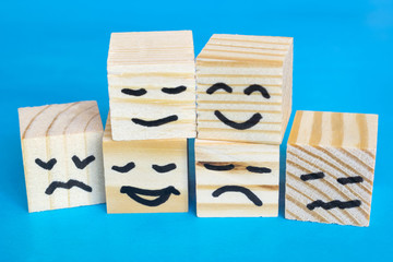 Different emotions drawn on wooden cubes on the blue background.