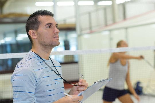 teacher giving badminton lesson