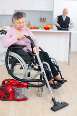 senior woman in wheelchair cleaning his house