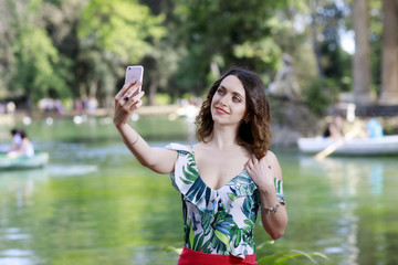 Girl take a selfie and smile. In the background the green lake in the outdoor park.