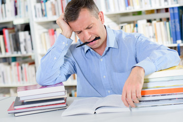 Frowning man reading with pen in mouth