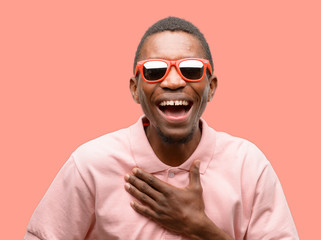 African black man wearing sunglasses confident and happy with a big natural smile laughing