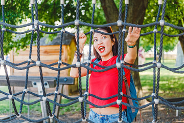 Adult woman is playing on the playground or at rope amusement and adventure park