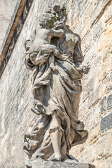 Statue of old priest with baby at Old Town in Prague, Czech Republic