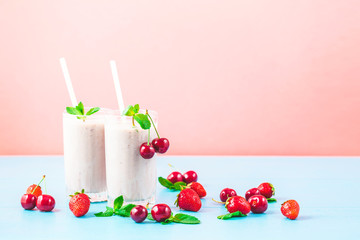 Two glasses of milk smoothies with cherries, strawberries, banana and mint on bright background Concept of a healthy lifestyle. Place for copy space Tasty and healthy weight loss