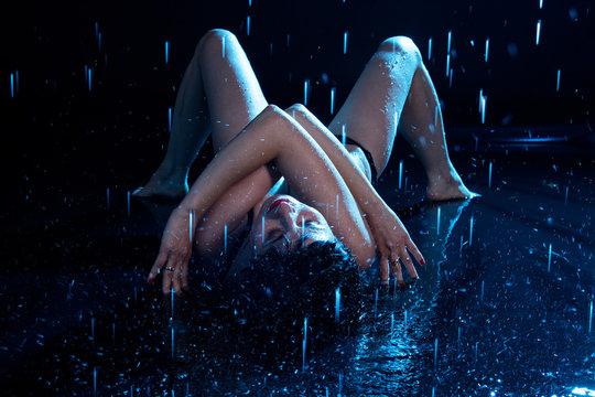 Girl in swimsuit under a drop of water, shooting in aqua studio