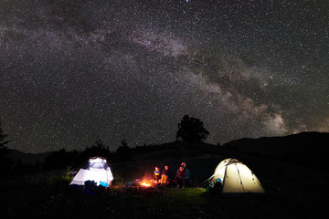 Family tourists mother, father, two children resting at night camping in mountains, sitting on log beside campfire and two illuminated tents, enjoying amazing view of sky full of stars, Milky way