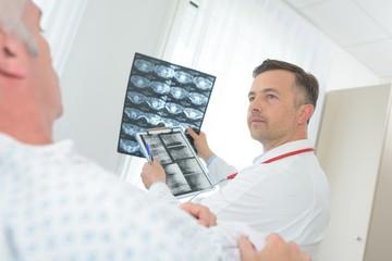 doctor examining x-ray image in hospital room