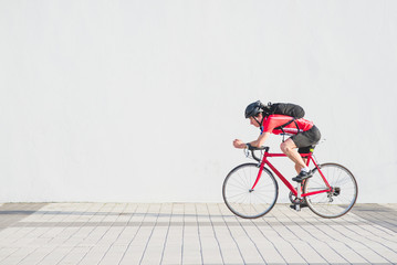 Side view photo of a professional cyclist in red sportswear and a helmet riding a red road bike on a white background. Porterter athlete cyclist on the background of a light wall. Copyspace