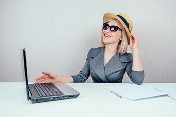 attractive woman blonde (business lady) in stylish business suit , in sunglasses and a straw hat dreams about vacation and sunbathing in office with laptop on the table. travel concept and holiday