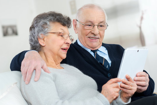 elderly couple holding a tablet