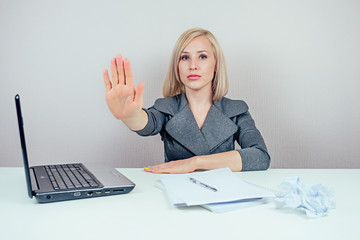 attractive strict blonde woman (business lady) in stylish business suit shows a hand gesture stop with laptop and a bunch of folders in the workplace office