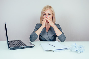attractive smart blonde multitasking woman (business lady) in stylish business suit working with laptop and a bunch of folders sick the flu in office . concept quarantine and deadline