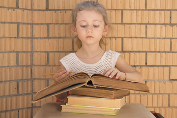 little girl reading a thick book on a stack of books on a brick wall background