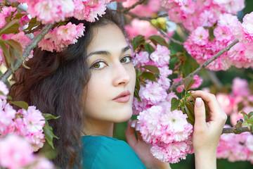 beautiful girl posing near pink sakura flowers as background, face closeup, spring landscape