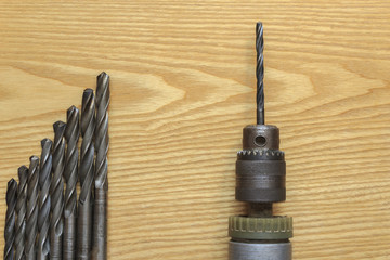 The old drill and drill bits on wooden background