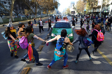Demonstrators surround a police vehicle during a march demanding an end to sexism and gender violence in Santiago