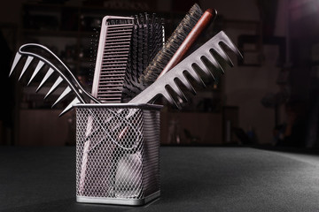 metal basket with various combs standing on a table in a salon. concept of professional hair caring tools. free space for advertising