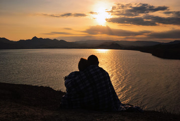 Loving couple admiring the sunset against the sea