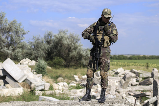 The soldier with the walkie-talkie and a gun on the background of the ruins