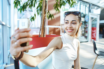Young smiling attractive woman sitting in coffee shop in the mall and making selfie on the phone