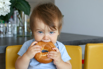 Portrait of cute baby boy with stylish haircut holding and eating big bagel sitting on yellow chair at home kitchen looking at camera