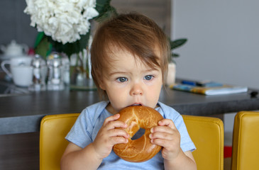 Portrait of cute thoughtful baby boy with stylish haircut holding and eating big bagel with open mouth, sitting on yellow chair at home kitchen