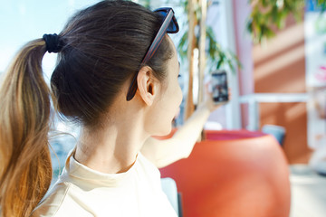 back view of a young smiling attractive woman sitting in coffee shop in the mall and making selfie on the phone