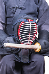 swordsman wear protective equipment 'bogu' and bamboo sword 'sinai'  for Japanese fencing Kendo training seat down