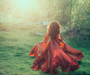A brunette girl with wavy, thick hair runs to the meeting of the sun. Photo from the back, without a face. The princess has a luxurious, chiffon, red dress that flutters in the wind. Background sunset