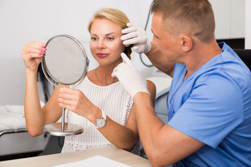 Specialist is analysing skin of female patient with using mirror before the procedure