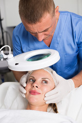 Man doctor is analysing skin on face of female patient before the procedure
